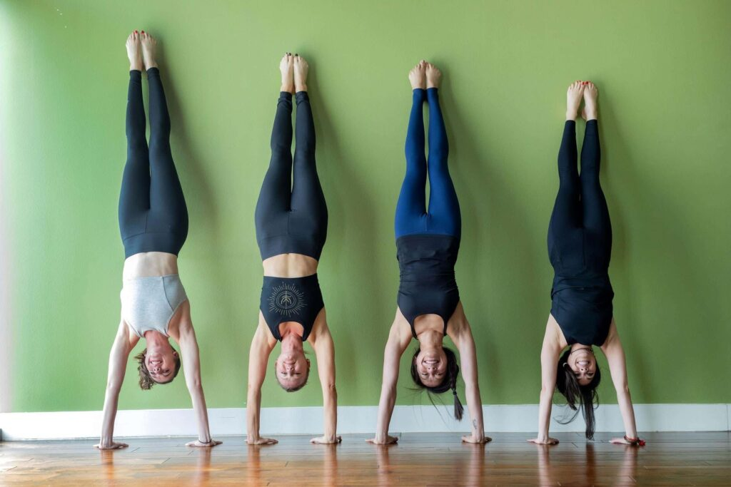 A group of people doing a Handstand pose